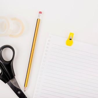 Close-up da página única; lápis; tesoura e fita de violoncelo no fundo branco