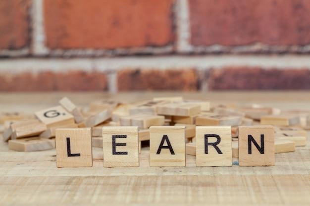 Close up da palavra aprender no bloco de madeira