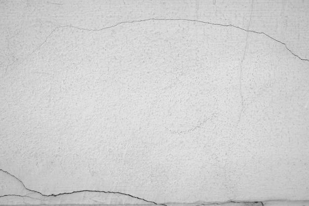 Close-up da parede da rachadura do cimento branco e da pintura descascada causada pela água e pela luz solar. descasque a parede da pintura de casa branca com mancha preta. preto e branco de fundo de textura.