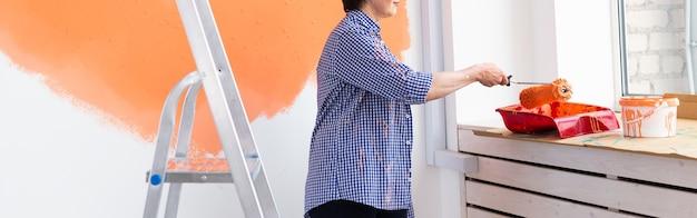 Close-up da parede de pintura de mulher de meia-idade. conceito de renovação, redecoração e reparo.