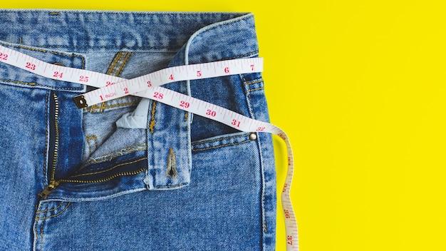 Close-up da parte superior do jeans azul e fita métrica