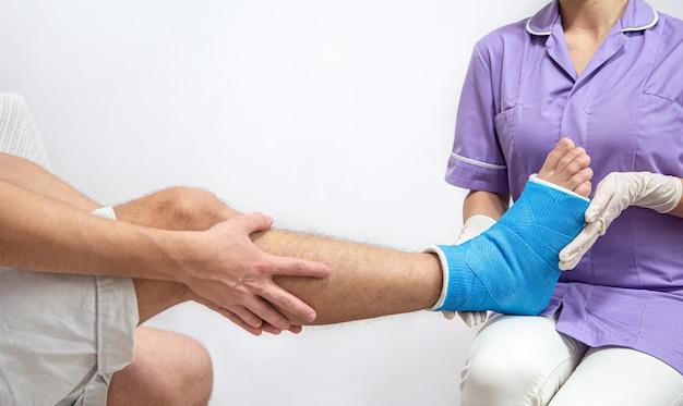 Close-up da perna de um homem engessada e uma tala azul após enfaixamento em um hospital.