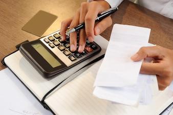 Close up da pessoa que prende contas e calculando-as