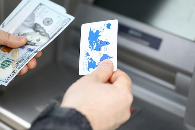 Close-up da pessoa segurando o cartão de crédito plástico e a pilha de notas. tiro macro da máquina de dinheiro moderna para obter salário ou pensão. conceito de tecnologia e finanças
