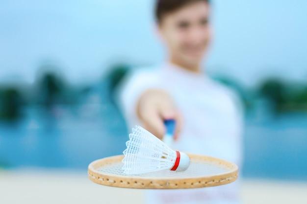 Close up da peteca branca que encontra-se na raquete de badminton de madeira.