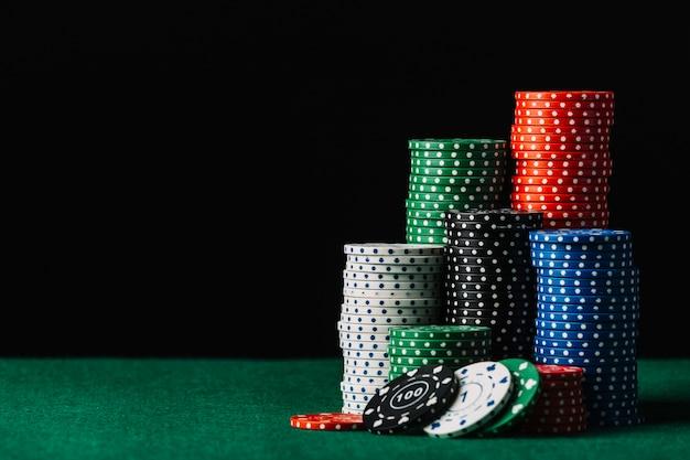 Close-up da pilha de fichas de casino na mesa de poker verde