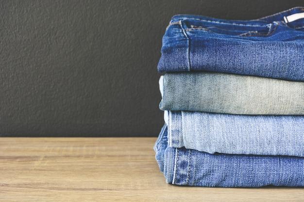 Close-up da pilha de jeans dobrado azul jeans na mesa de madeira