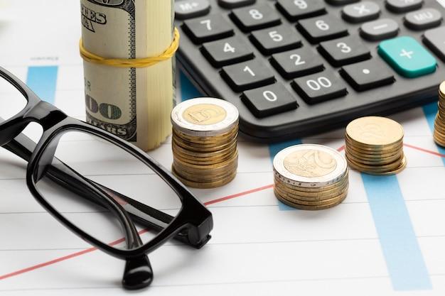 Close-up da pilha de moedas perto da pilha de notas