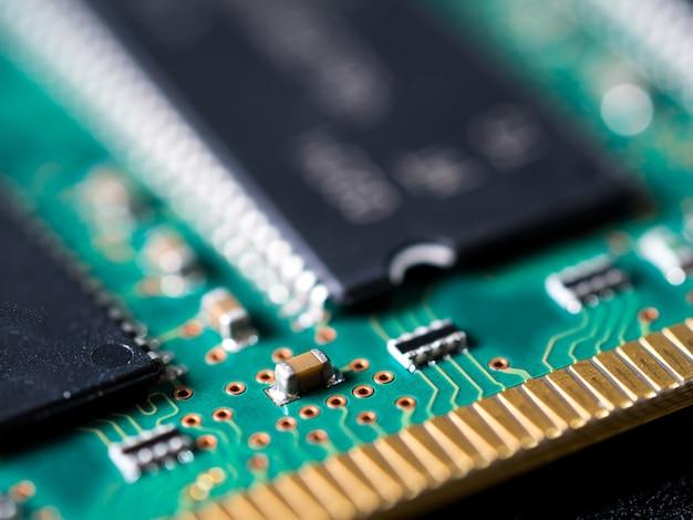 Close-up da placa de circuito com circuitos integrados, resistências e capacitores.