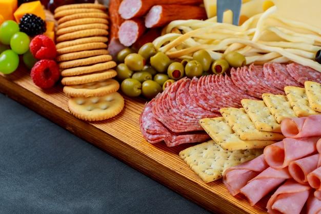 Close up da placa de corte com salame cortado, biscoitos e queijo sortido.