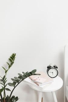 Close-up da planta com despertador, nota adesiva e livros no banquinho contra a parede