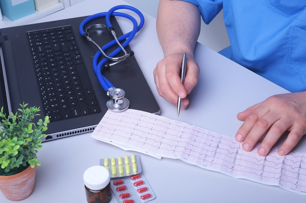 Close-up da prescrição de caligrafia do médico e segurando a garrafa com comprimidos.