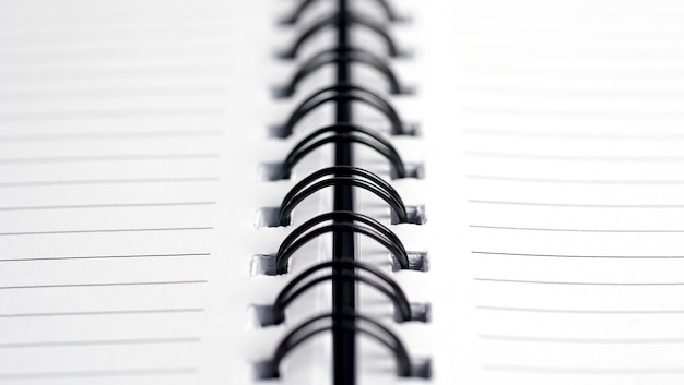 Close up da profundidade de campo rasa do caderno de metal espiral.