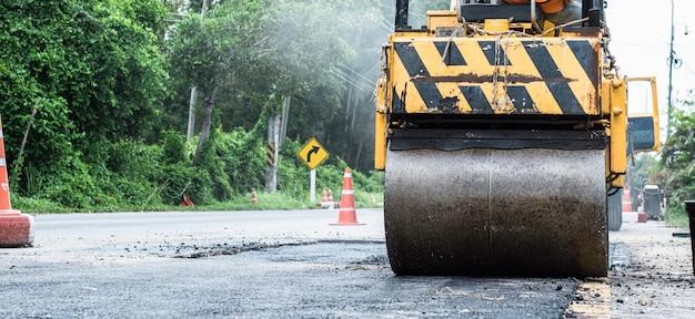 Close up da roda de aço de um rolo pequeno do asfalto dentro no dever que repara reparando a estrada asfaltada. trabalhadores na construção de estradas, indústria e trabalho em equipe.