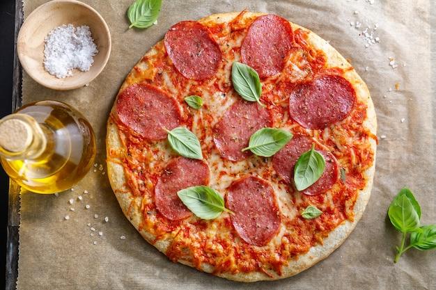 Close up da saborosa pizza de salame apetitoso com queijo e especiarias.