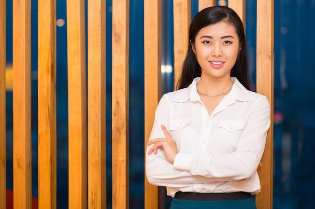 Close up da senhora elegante asiática na divisória de madeira
