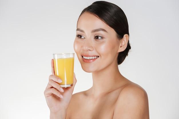 Close-up da senhora seminua com pele fresca saudável e sorriso amplo, bebendo suco de laranja de vidro transparente, isolado sobre a parede branca