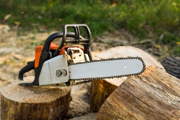 Close-up da serra de cadeia de serrar lenhador em movimento, serragem voar para os lados. uma pessoa que usa uma serra elétrica na bonita madeira. lenhador vê árvore com serra elétrica na serraria