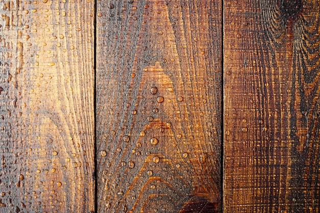Close up da superfície de madeira em gotas de água textura de madeira molhada gotas de água em uma placa de madeira rústica em.