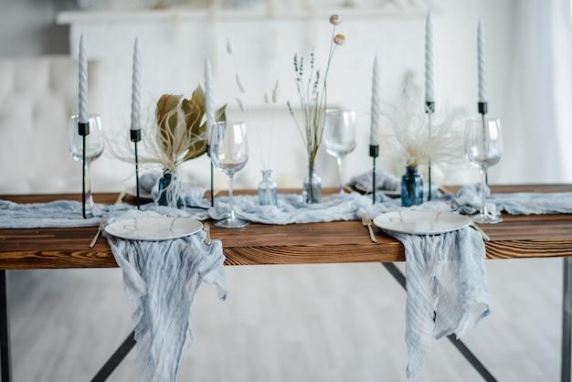 Close up da tabela de madeira do jantar na cor azul empoeirada. chapa branca com vintage dourado garfo e faca, velas em castiçais, guardanapos de gaze. jantar de casamento. decoração.