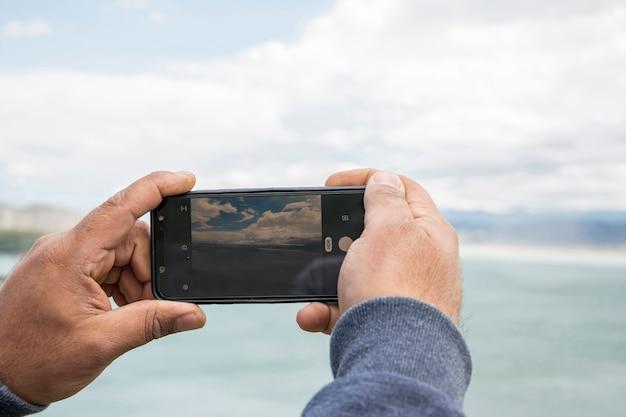 Close-up da tela da câmera smartphone fotografando bela paisagem