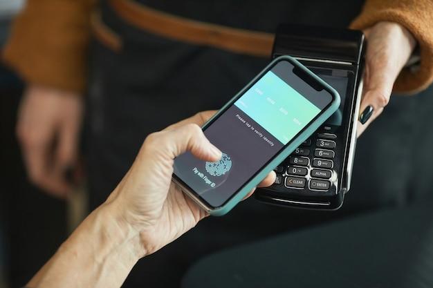 Close-up da tela irreconhecível do cliente tocando para ativar o aplicativo com impressão digital usando o smartphone ao pagar por nfc no café