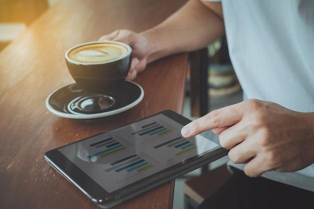 Close-up da tela tocante de dedo no tablet com documento comercial financeiro na cafeteria.
