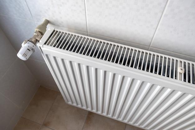 Close up da válvula do radiador de aquecimento para uma regulação confortável da temperatura no radiador de metal na parede inferior.