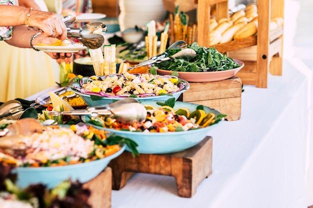 Close-up da vista de uma mesa cheia de comida com alguém pegando macarrão da mesa para comemorar