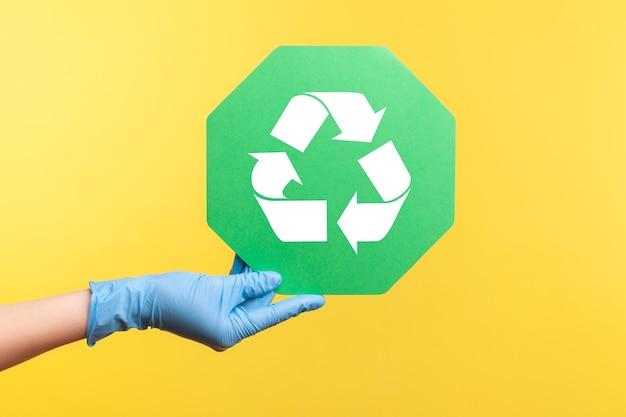 Close up da vista lateral do perfil da mão humana em luvas cirúrgicas azuis segurando o cartaz de reciclagem.