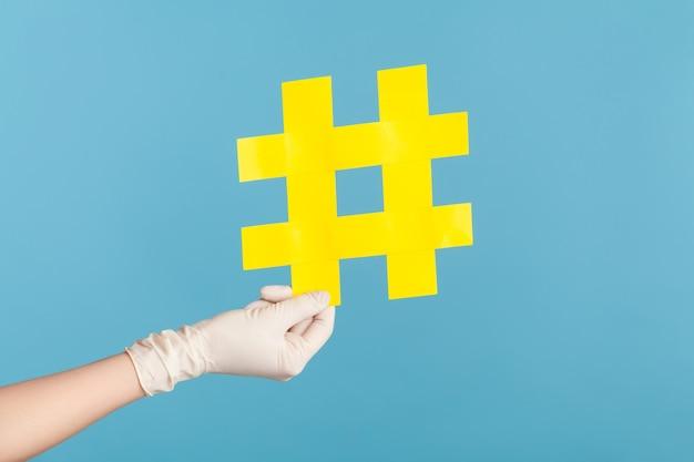 Close up da vista lateral do perfil da mão humana em luvas cirúrgicas brancas segurando uma hashtag amarela.