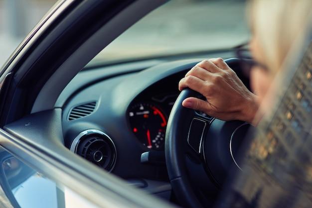 Close-up da vista traseira de uma mulher dirigindo um carro pela cidade