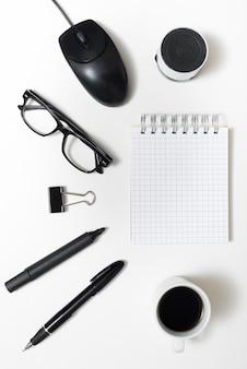 Close-up da xícara de café; papelaria de escritório; óculos; e alto-falante bluetooth com o bloco de notas sobre o pano de fundo branco