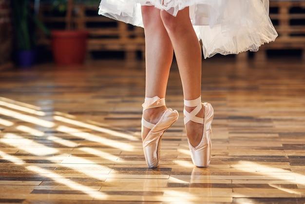 Close-up dançando as pernas da bailarina usando sapatilhas de ponta branca no salão de dança.