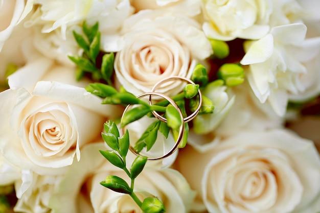 Close-up das alianças de casamento no ramalhete. decoração do casamento