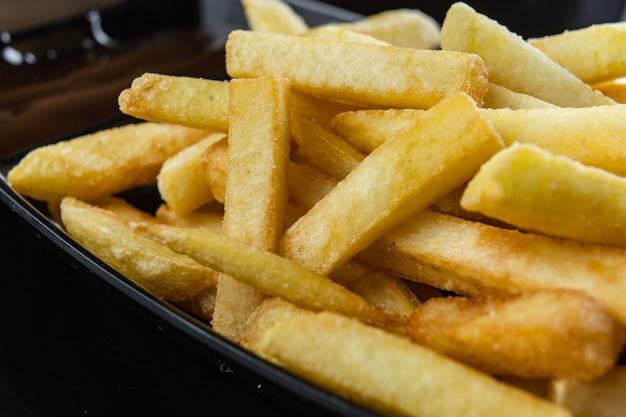Close-up das batatas fritas na placa preta com molho.