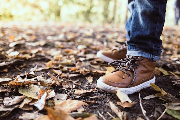 Close up das botas da criança no fundo brilhante das folhas de outono.