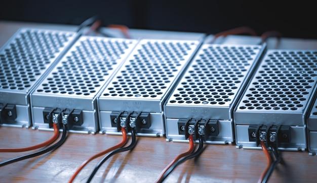 Close up das caixas de malha de metal da fonte de alimentação e fios estão em uma mesa de madeira na produção de computadores de alta tecnologia. conceito de alta tecnologia e informática