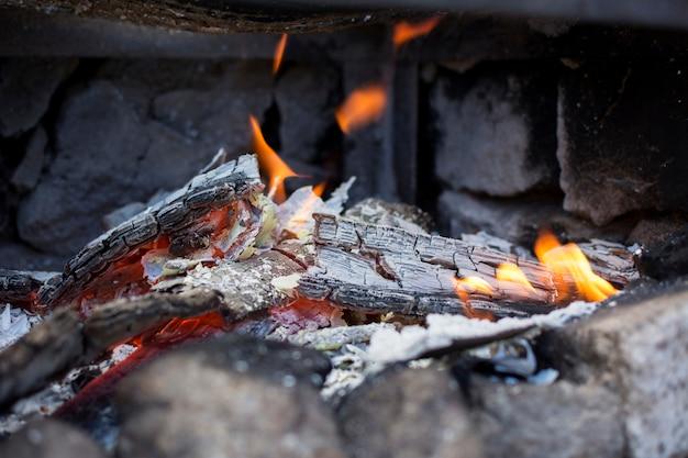 Close-up das cinzas e chamas de uma grade.