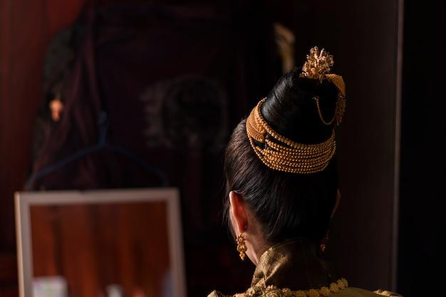 Close-up das costas da noiva do laos, sentada no espelho na sala