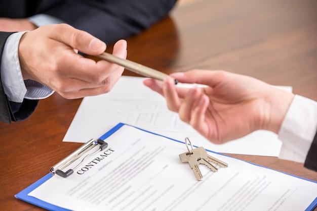 Close-up das mãos com uma caneta para assinar um contrato.