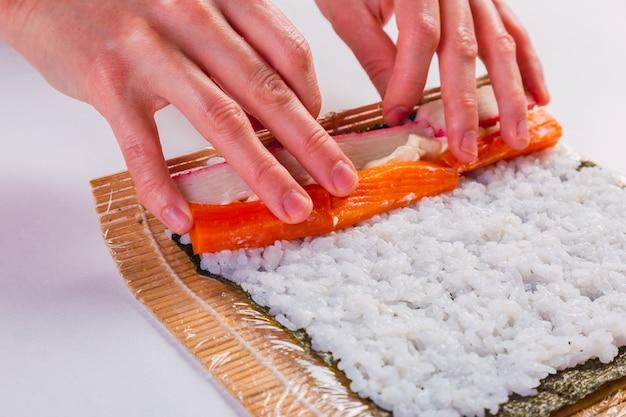 Close-up das mãos da cozinheira fazendo sushi - processo de preparação.