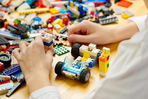 Close-up das mãos da criança brincando com tijolos de plástico coloridos na mesa, desenvolvimento de habilidades motoras finas em crianças favoráveis para o desenvolvimento da atividade cerebral, desenvolvendo brinquedos