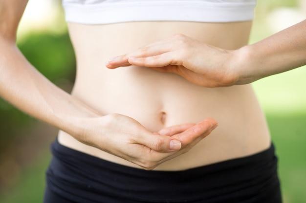 Close-up das mãos da jovem mulher e da barriga magro