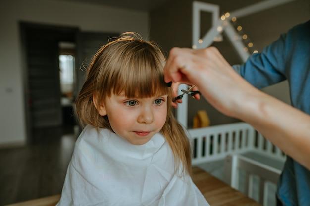 Close-up das mãos da mãe feminina, cortando o cabelo de sua filha de quatro anos em casa, no quarto de crianças. rotina diária em casa.