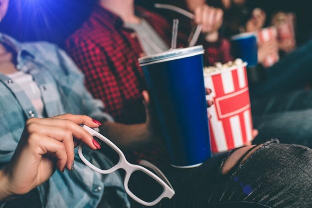 Close-up das mãos da menina, mantendo os óculos e um copo azul de coca-cola