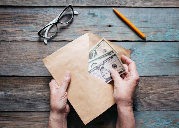Close-up das mãos da mulher coloca notas de dólar americano em um envelope na área de trabalho de madeira
