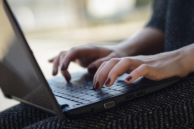 Close-up das mãos da mulher com unhas pintadas digitando no laptop