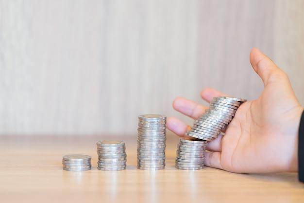 Close up das mãos da mulher de negócios com moedas de pilha - estoque e mercado para baixo