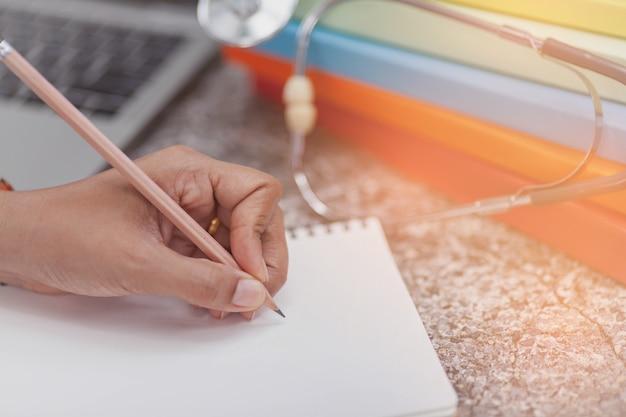 Close-up das mãos da mulher escrevendo no bloco de notas em espiral, colocado na área de trabalho com vários itens